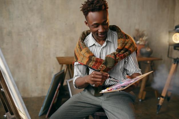 Uśmiechnięty malarz z pędzlem i paletą siedzący przy sztalugach. mężczyzna artysta rysuje w swoim miejscu pracy, twórca pracuje w warsztacie