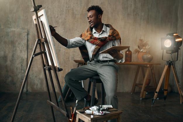 Uśmiechnięty malarz z pędzlem i paletą siedzący przy sztalugach. mężczyzna artysta rysuje w swoim miejscu pracy, twórczy mistrz pracuje w warsztacie