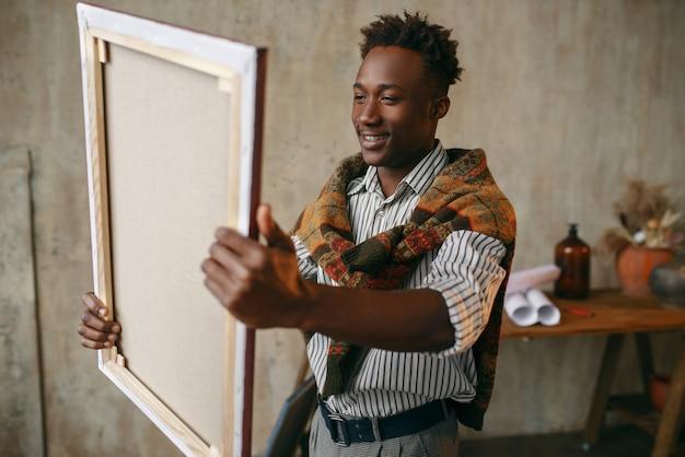 Uśmiechnięty malarz z płótnem stojącym w pobliżu sztalugi. mężczyzna artysta rysuje w swoim miejscu pracy, twórczy mistrz pracuje w warsztacie