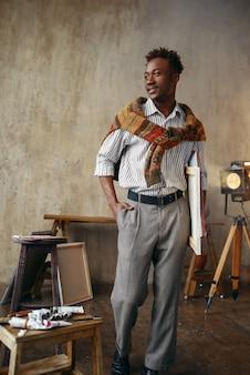 Uśmiechnięty malarz z płótnem stojącym w pracowni artystycznej. mężczyzna artysta rysuje w swoim miejscu pracy, twórczy mistrz pracuje w warsztacie