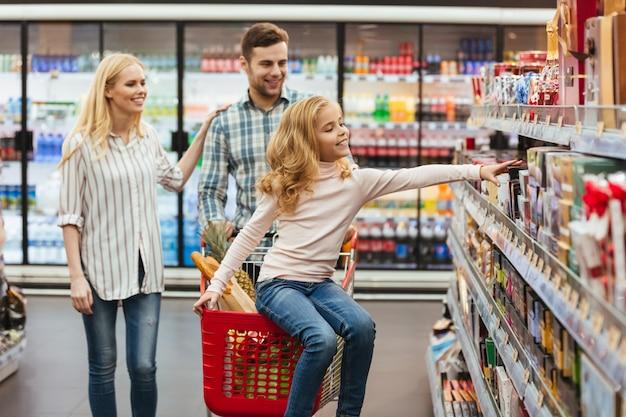 Uśmiechnięty małej dziewczynki obsiadanie na wózek na zakupy