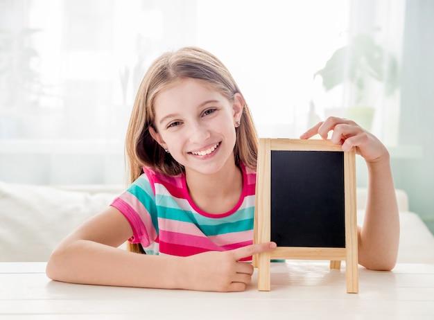 Uśmiechnięty małej dziewczynki obsiadanie przy stołem z pustym małym chalkboard