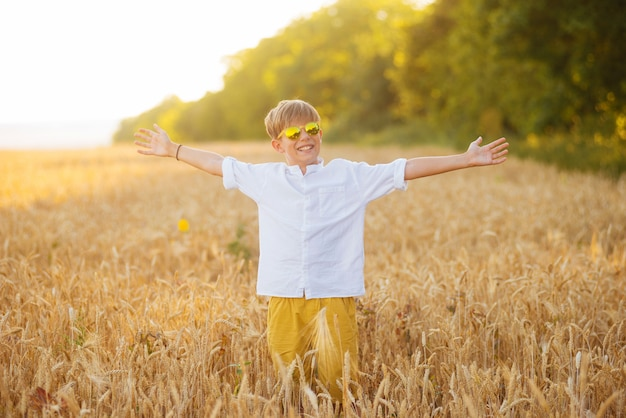 Uśmiechnięty mały chłopiec blondynka z szeroko otwartymi ramionami stoi pośrodku pola upraw.