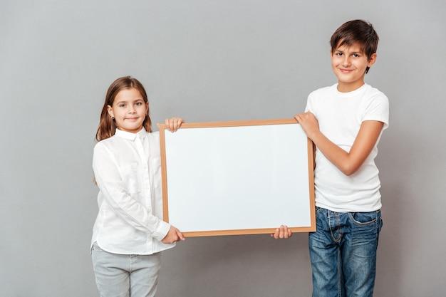 Uśmiechnięty mały chłopiec i dziewczynka stojący i trzymający pustą białą tablicę