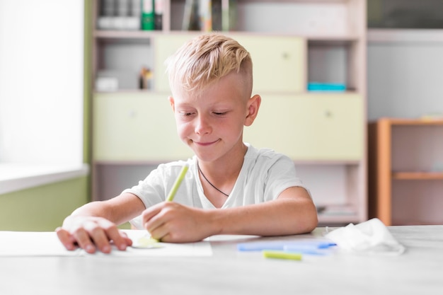 Uśmiechnięty mały chłopiec pisze