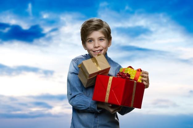 Uśmiechnięty mały chłopiec trzyma stos prezentów