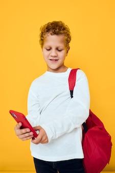 Uśmiechnięty mały chłopiec używa telefonu edukacja dzieci styl życia na białym tle