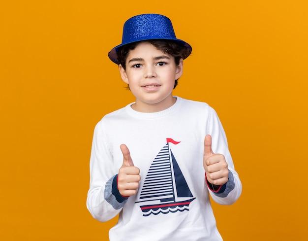 Uśmiechnięty mały chłopiec w niebieskiej imprezowej czapce pokazujący kciuki do góry odizolowany na pomarańczowej ścianie