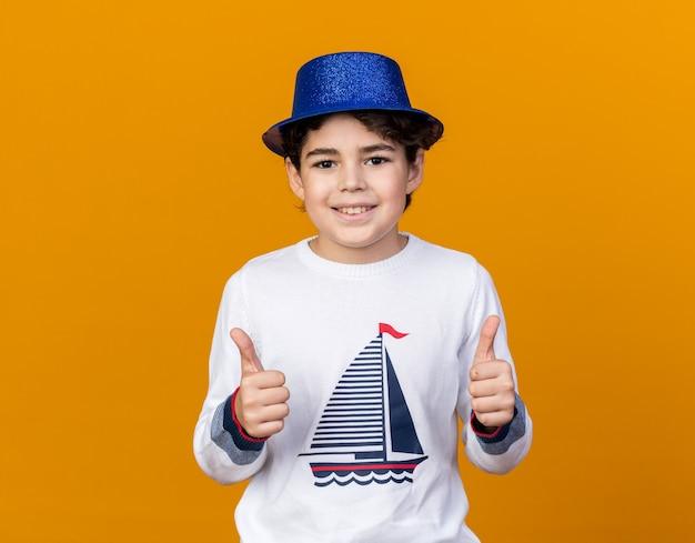 Uśmiechnięty mały chłopiec w niebieskiej imprezowej czapce pokazujący kciuki w górę