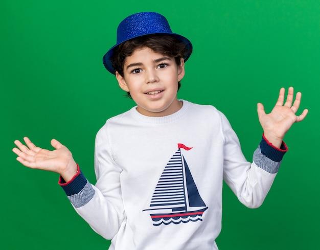 Uśmiechnięty mały chłopiec w niebieskiej imprezowej czapce rozkładający ręce