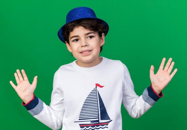 Uśmiechnięty mały chłopiec w niebieskim kapeluszu imprezowym rozkładającym ręce na zielonej ścianie