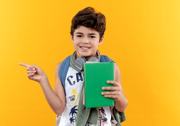 Uśmiechnięty mały chłopiec w szkole noszenie plecaka i słuchawek, trzymając książkę i punkty po stronie na białym tle na żółto z miejsca na kopię