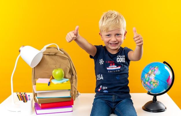 Uśmiechnięty mały chłopiec w szkole siedzący na stole z szkolnymi narzędziami pokazującymi kciuk w górę