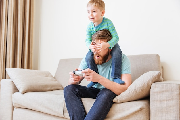 Uśmiechnięty mały chłopiec zasłaniający oczy swojego ojca podczas grania w gry komputerowe na kanapie w domu