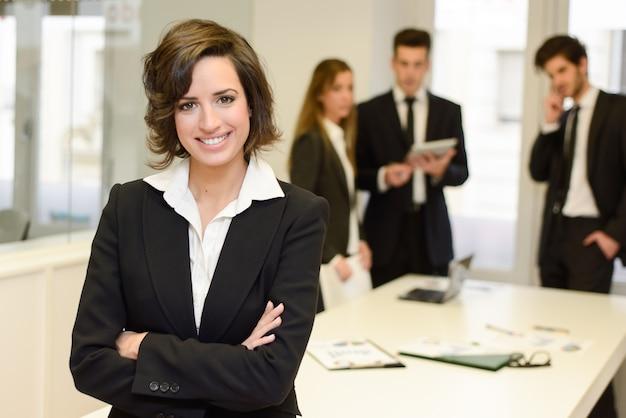 Uśmiechnięty manager brunetka ze skrzyżowanymi rękami