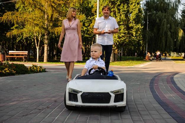 Uśmiechnięty mąż i żona chodzą po bruku alei w zielonym parku podążają za synem w samochodzie