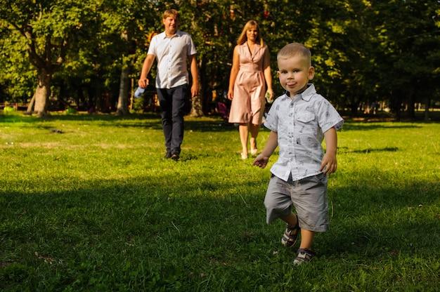 Uśmiechnięty mąż i żona spaceru na trawie w zielonym parku podążają za synem