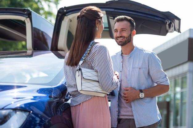 Uśmiechnięty mąż. przystojny mąż uśmiechający się rozmawiając ze swoją atrakcyjną ciemnowłosą żoną