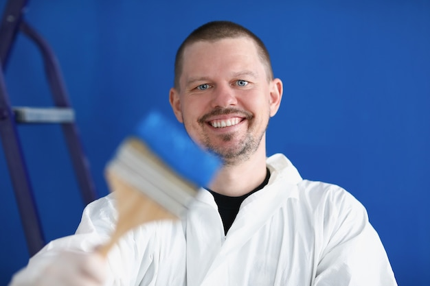 Uśmiechnięty mechanik trzymający pędzel budowlany z niebieską farbą
