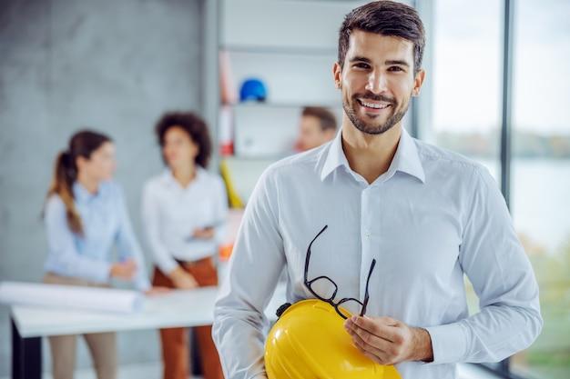 Uśmiechnięty męski architekt trzymając kask i okulary, patrząc na przód