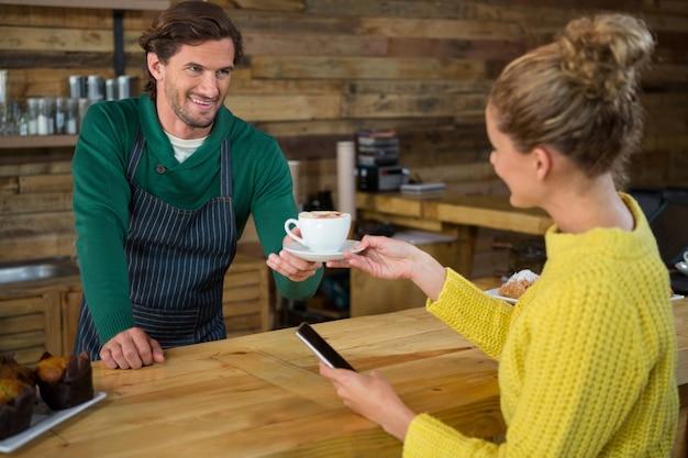 Uśmiechnięty męski barista obsługujący kawę klientowi płci żeńskiej w kawiarni