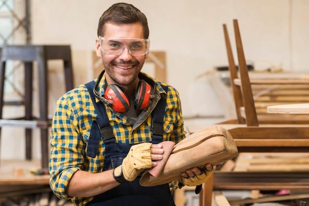 Uśmiechnięty męski cieśla gładzi drewnianą strukturę z piaska papierem
