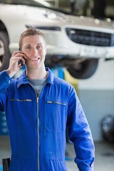Uśmiechnięty męski mechanik na wezwaniu