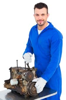 Uśmiechnięty męski mechanik naprawia samochodowego silnika
