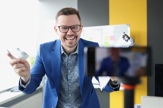 Uśmiechnięty męski mentor wprowadzi koncepcję zdalnego uczenia się bloga o rozwoju biznesu online