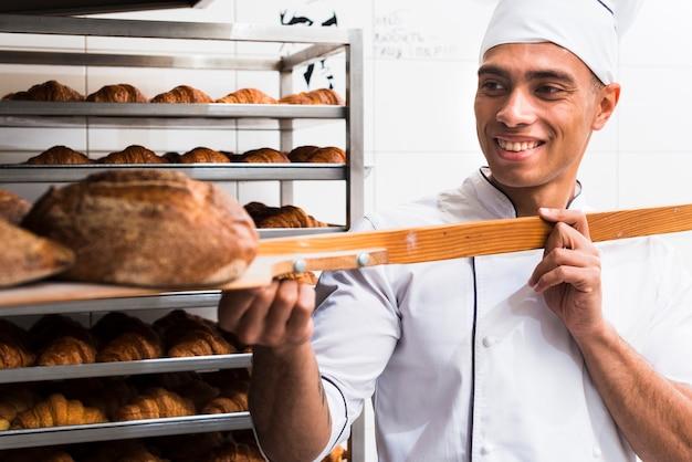 Uśmiechnięty męski piekarz w mundurze wyjmuje z łopatą świeżo piec chleb z piekarnika