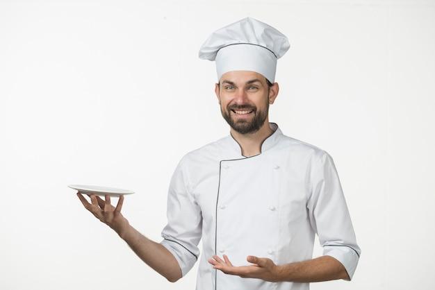 Uśmiechnięty męski szef kuchni przedstawia jego naczynie przeciw białemu tłu