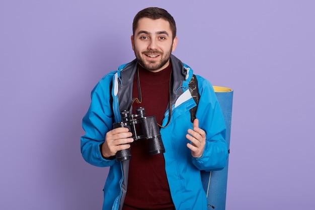 Uśmiechnięty męski turysta patrząc na kamery i trzymając w rękach lornetkę