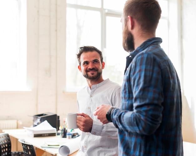 Uśmiechnięty męski współpracownik opowiada podczas przerwy