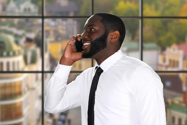 Uśmiechnięty mężczyzna afro z telefonem komórkowym.