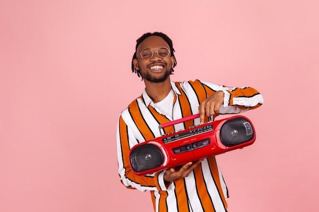 Uśmiechnięty mężczyzna afroamerykański naciskający przycisk odtwarzania na magnetofonie, cieszący się słuchaniem taśm retro