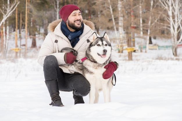 Uśmiechnięty mężczyzna azji z psem w zimie