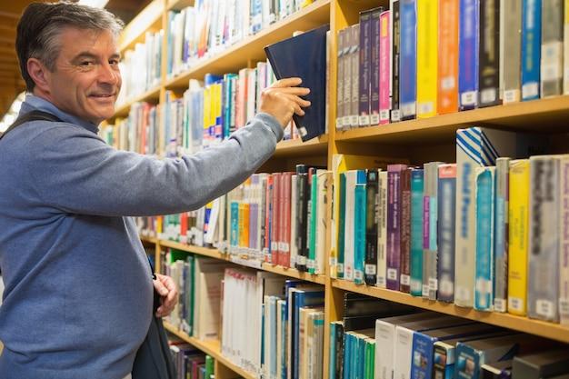 Uśmiechnięty mężczyzna bierze książkę od półek