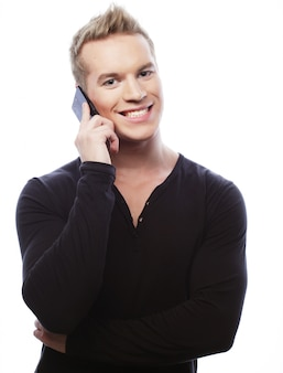 Uśmiechnięty mężczyzna chodzi i opowiada na telefonie komórkowym