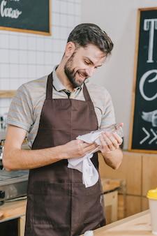 Uśmiechnięty mężczyzna czyści szkło