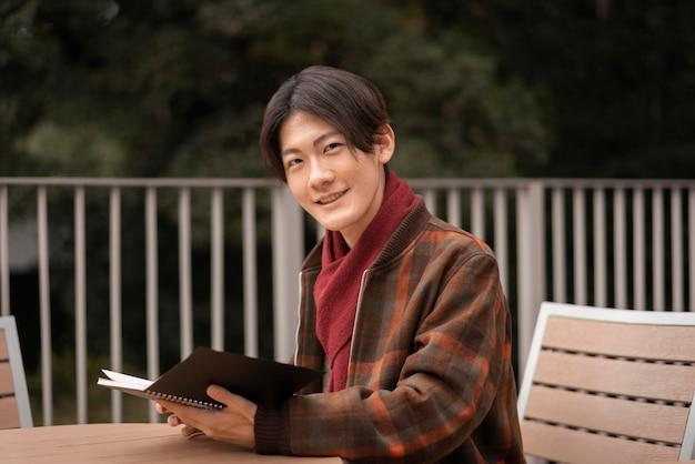 Uśmiechnięty mężczyzna czytający na zewnątrz na stole