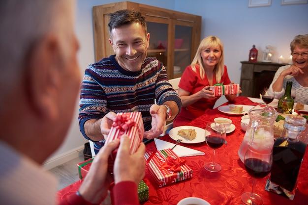 Uśmiechnięty mężczyzna daje prezent swojemu ojcu