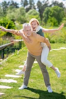 Uśmiechnięty mężczyzna daje żonie przejażdżkę na barana
