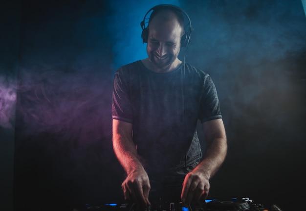 Uśmiechnięty mężczyzna dj pracuje pod światłami w ciemności