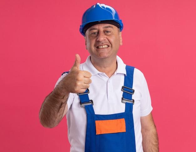 Uśmiechnięty mężczyzna dorosły kaukaski konstruktora w jednolite kciuki do góry na białym tle
