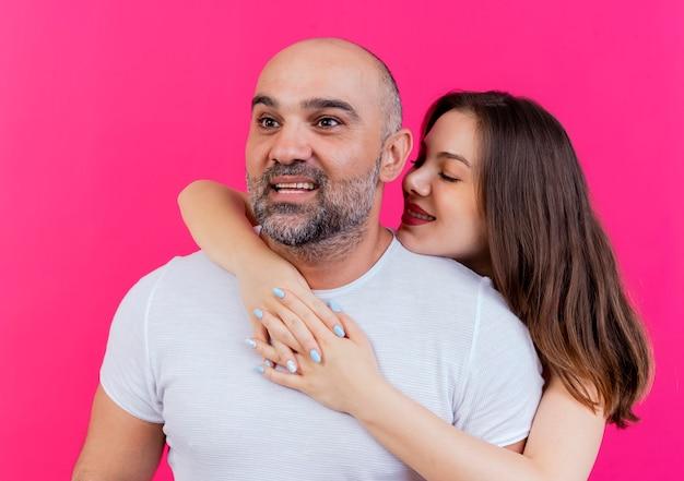 Uśmiechnięty mężczyzna dorosły para patrząc na boku kobieta kładąc dłoń na jego ramieniu trzymając ręce razem patrząc na niego