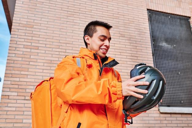 Uśmiechnięty mężczyzna dostawy latino z kaskiem rowerowym i plecakiem