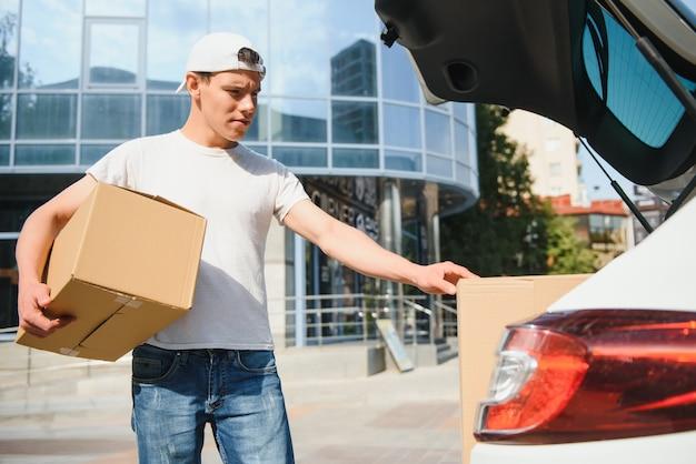Uśmiechnięty mężczyzna dostawy stojący przed swoim samochodem