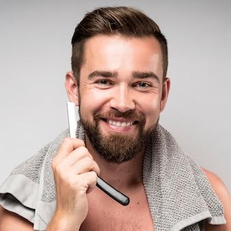 Uśmiechnięty mężczyzna goli brodę