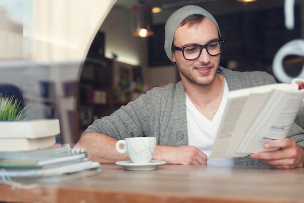 Uśmiechnięty mężczyzna hipster czytanie książki w kawiarni