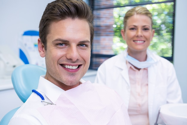Uśmiechnięty mężczyzna i dentysta siedzi w klinice stomatologicznej